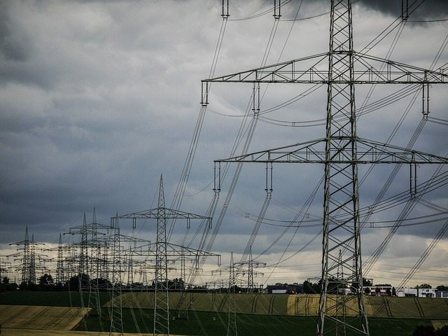string of power lines in front of a cloudy, grey sky